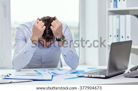 business, people, paperwork and deadline concept - stressed businessman with papers and charts sitting at table in office - stock photo