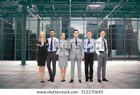 business, people, partnership and cooperation concept - group of smiling businesspeople over empty urban city construction background - stock photo