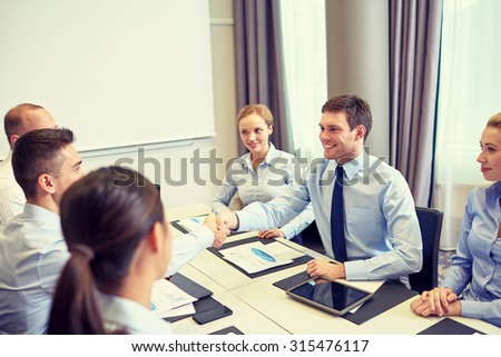 business, people, partnership, gesture and startup concept - group of smiling business people meeting and shaking hands in office - stock photo