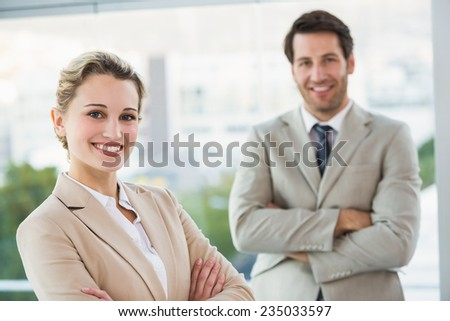 Business people posing with arms crossed smiling at camera in office - stock photo