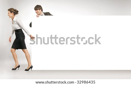 Business people pulling an empty white board, lots of copyspace - stock photo