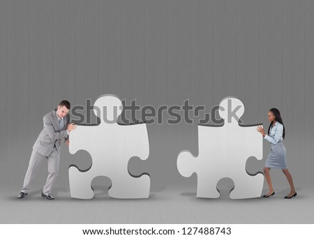 Business people pushing two jigsaw pieces together on grey background - stock photo