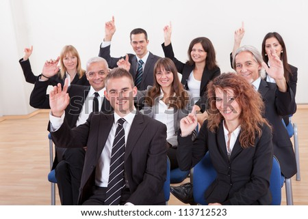 Business People Raising Their Hand In A Seminar - stock photo
