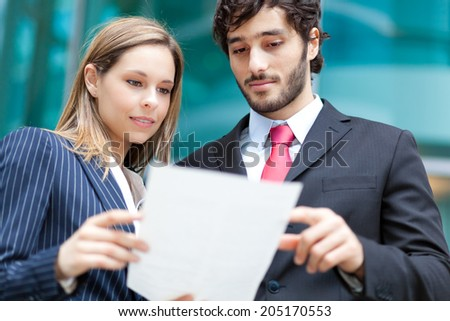 Business people reading a document - stock photo