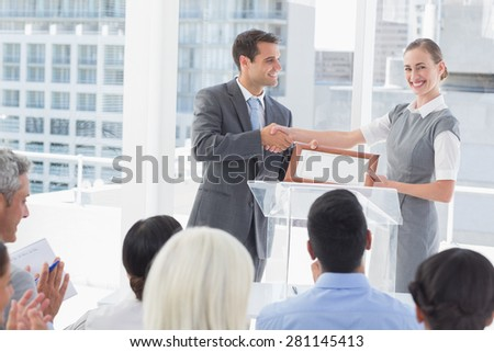 Business people receiving award in meeting room - stock photo