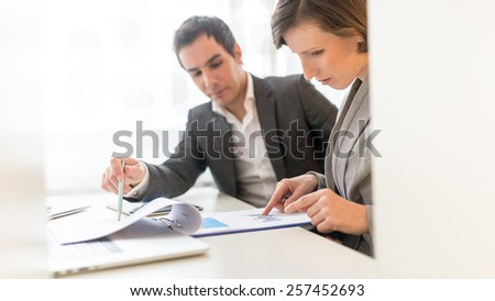 Business People Reviewing Business Reports Seriously While Sitting at the Worktable. - stock photo