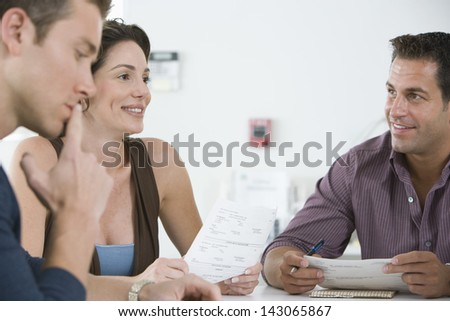 Business people reviewing documents during meeting in conference room - stock photo