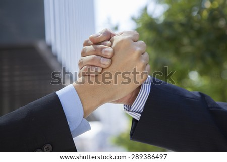 Business people shaking hands outside modern office building.  - stock photo