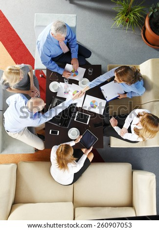 Business people shaking hands while sitting at business meeting.  - stock photo