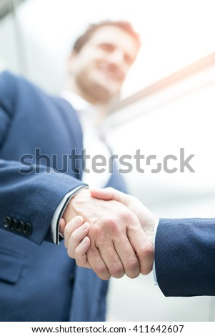 business people shaking hands with office window - stock photo