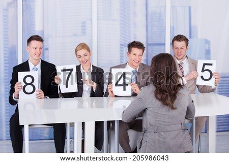 Business people showing score cards in front of female candidate during interview - stock photo