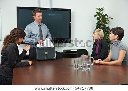 Business people sitting around meeting table in board room. - stock photo
