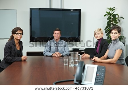 Business people sitting around meeting table in board room, waiting, looking at camera. Blank space on screen for your logo or text. - stock photo