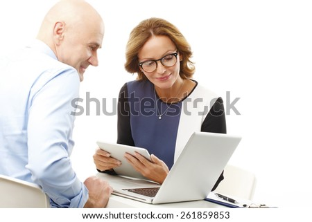 Business people sitting at desk in front of laptop and consulting. Isolated on white background.  - stock photo