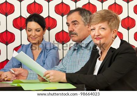 Business people sitting at meeting table and doing different things - stock photo
