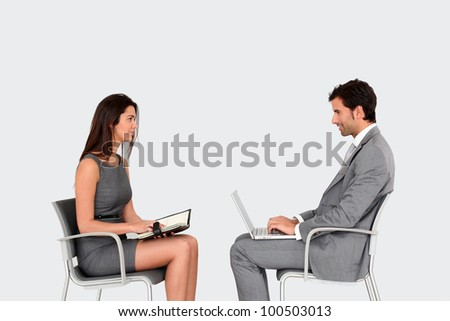 Business people sitting face to face on grey background - stock photo