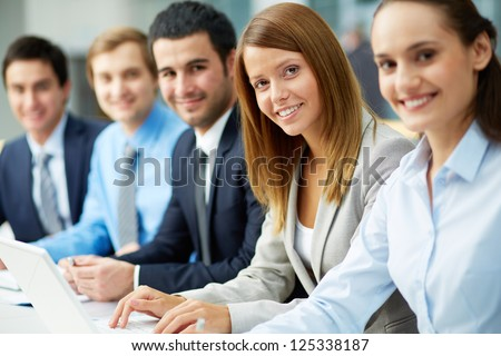 Business people sitting in a row and working, focus on pretty woman - stock photo