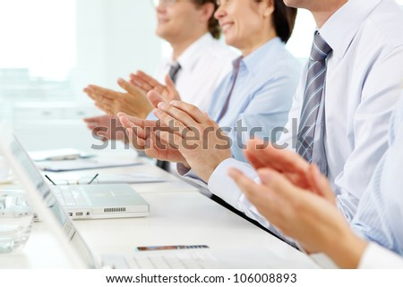 Business people sitting in a row applauding cheerfully to their successful colleague - stock photo