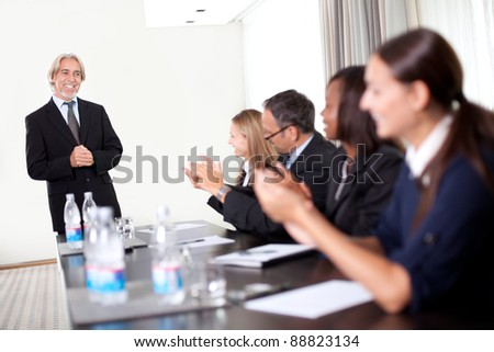 Business people sitting in a row at meeting and celebrating goal achievement - stock photo