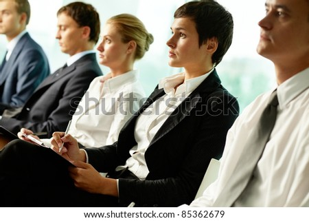 Business people sitting in a row at seminar - stock photo