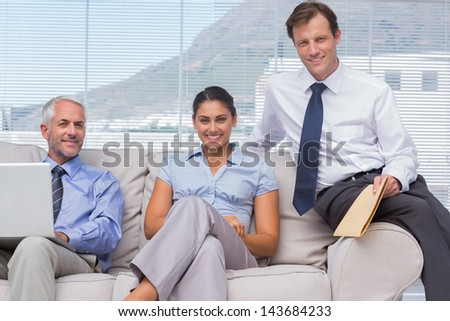 Business people sitting on sofa smiling at camera in staffroom - stock photo