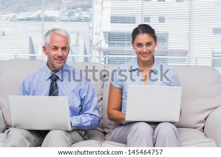 Business people sitting on sofa using their laptops and smiling at camera in staffroom - stock photo