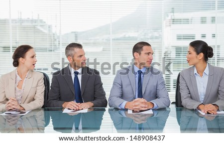 Business people sitting straight talking together in bright office - stock photo