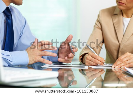Business people sitting together holding a discussion concerning new strategic movements - stock photo