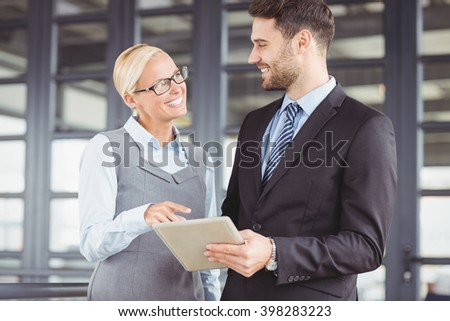 Business people smiling while discussing over digital tablet in office - stock photo