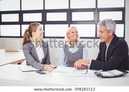 Business people smiling while discussing with client in meeting room - stock photo