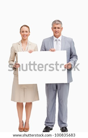 Business people smiling while holding a poster against white background - stock photo