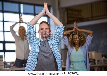 Business people smiling while practicing yoga in creative office - stock photo