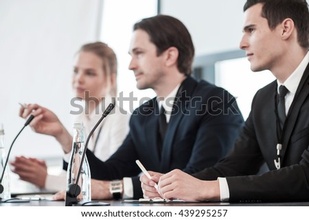 Business people speaking at presentation in microphones in office - stock photo