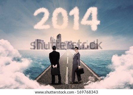 Business people standing on the road and looking at a cityscape on the horizon - stock photo