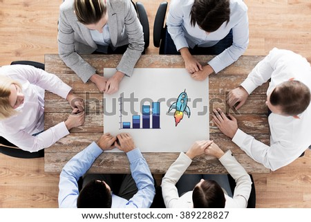 business, people, statistics, success and team work concept - close up of business group with cahrt and rocket doodle sitting at table in office - stock photo