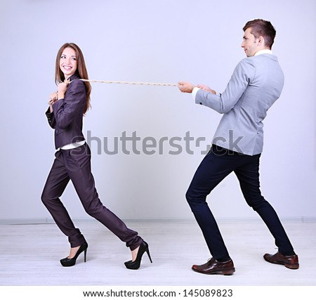 Business people stretching rope - stock photo