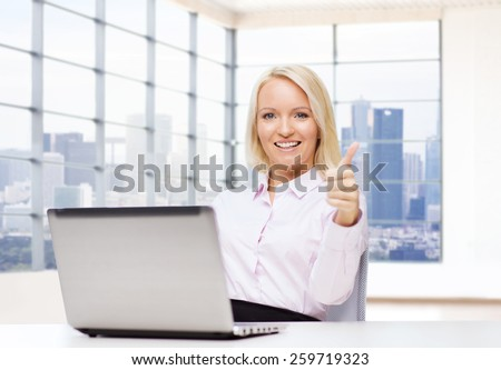 business, people, success, gesture and technology concept - smiling businesswoman or student showing thumbs up with laptop computer in office - stock photo