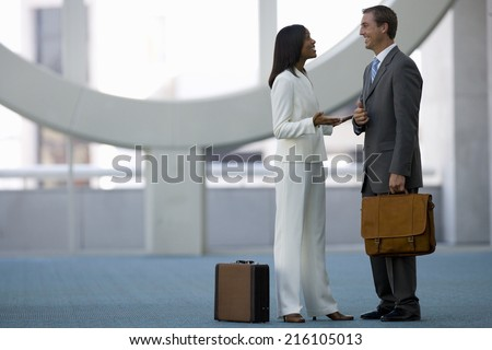 Business people talking in airport terminal - stock photo