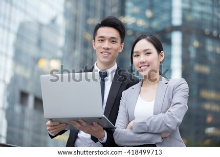 Business people team meeting with computer in front of the office building, shot in Hong Kong, asian - stock photo