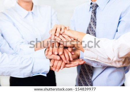 business people team putting their hands stack on top of each other, businesspeople colleagues pile of hand closeup, at office, concept of success collaboration leader - stock photo