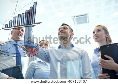 business, people, teamwork and planning concept - smiling business team drawing chart on notice board in office - stock photo