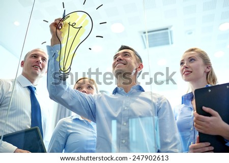 business, people, teamwork and planning concept - smiling business team with marker and light bulb doodle working in office - stock photo