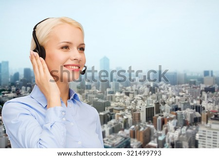 business, people, technology and communication concept - happy female helpline operator in headset over city background - stock photo