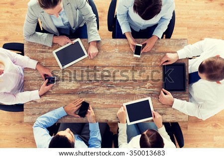 business, people, technology and team work concept - close up of creative team with smartphones and tablet pc computers sitting at table in office - stock photo