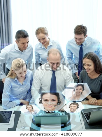business, people, technology and teamwork concept - smiling business team with laptop computer and virtual projection working in office - stock photo