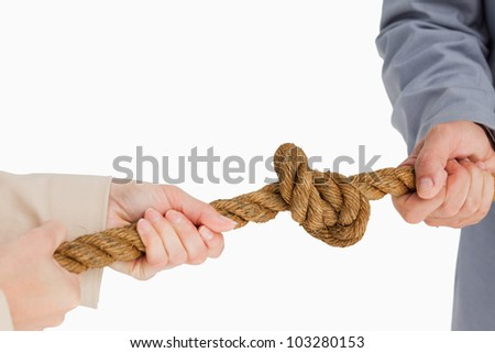 Business people tightening a knot against white background - stock photo