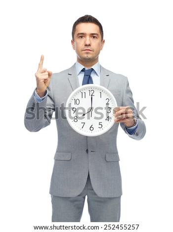 business, people, time management and gesture concept - businessman in suit holding clock showing 8 o'clock and pointing finger up - stock photo