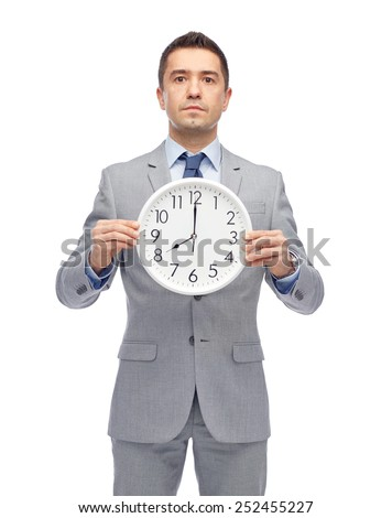 business, people, time management and office concept - businessman in suit holding clock showing 8 o'clock - stock photo
