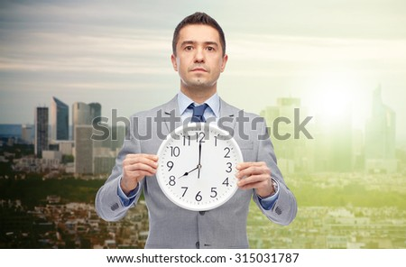business, people, time management and work concept - businessman in suit holding clock showing 8 o'clock over sunrise city background - stock photo