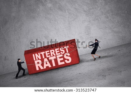 Business people trying to get a block with interest rates word on it - stock photo